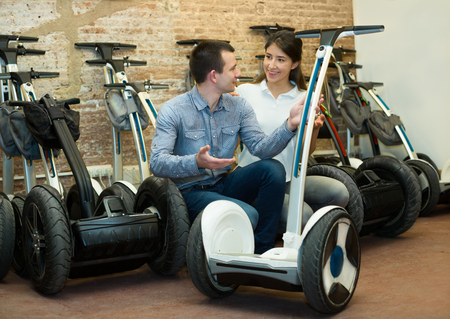 rental agency: Kindly female employee helping adult guy to select segway at a rental agency. Focus on man