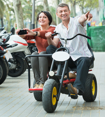 Adult smiling pleasant couple with double bike and camera in vacation on city street
