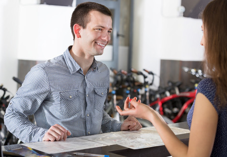rental agency: Happy young couple selecting a bikes at rental agency indoors. Focus on man Stock Photo