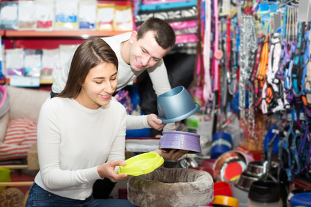 Portrait of young american couple purchasing pet bowls in petshop