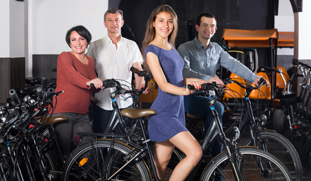 rental agency: Positive family of four selecting electric bikes at rental agency indoors. Selective focus