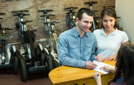 Portrait of caucasian girl executing documents to rental segways store