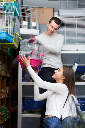 19's: Positive young couple buying cage for bird in shop. Focus on girl
