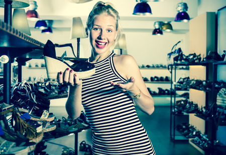desired: Adult woman shopaholic holding desired shoe in fashion boutique