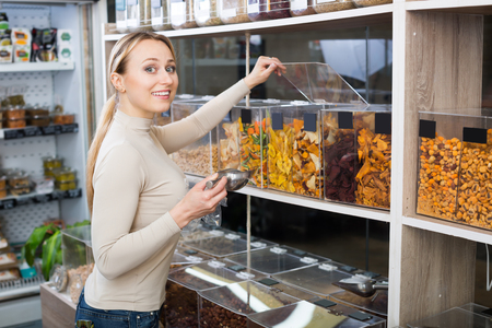 candied fruits: Young female customer selecting various candied fruits in the store with ecological goods Stock Photo