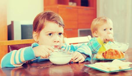 siblings: siblings eating dairy breakfast together Stock Photo