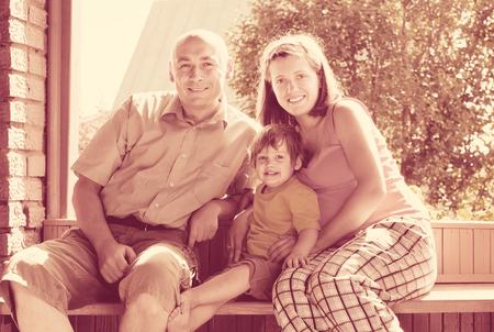 gravida: Happy parents with child sits on bench in veranda Stock Photo
