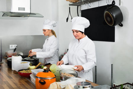 Cozinheiro Maduro De Sorriso Da Mulher Que Veste O Uniforme Que Está