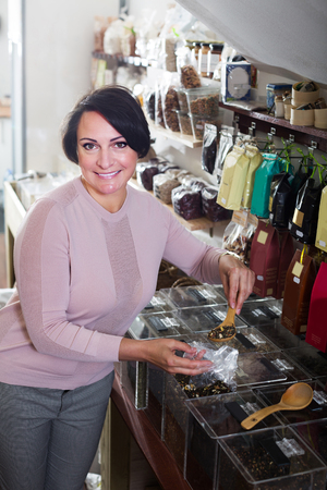 mature brunette: Happy mature brunette woman choosing tea sold by weight in organic shop Stock Photo