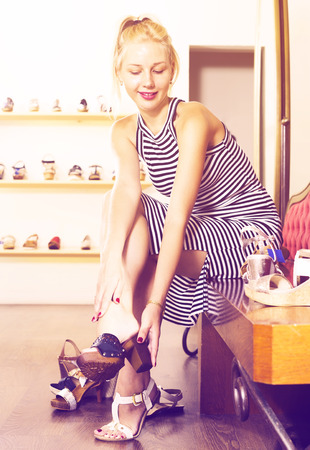 fitting in: portrait of young cheerful woman fitting picked footwear in store