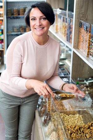 mature brunette: Positive mature brunette woman choosing nuts sold by weight in organic shop Stock Photo