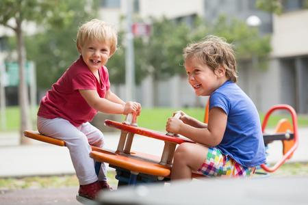 5s: Two happy little girls on teetering board outdoor