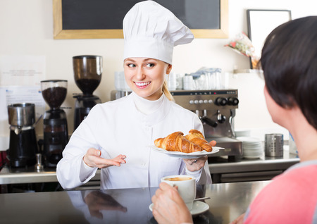 gladly: Positive young female cook gladly selling pastry to a customer in the cafeteria Stock Photo