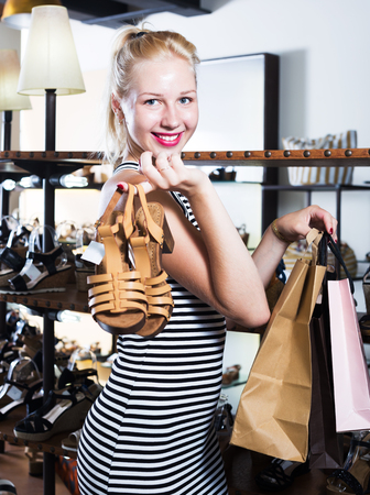 portrait of young postive girl with shopping bags and chosen pair of shoes in fashion department