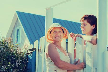 wicket: Two happy women near fence wicket  in front of home