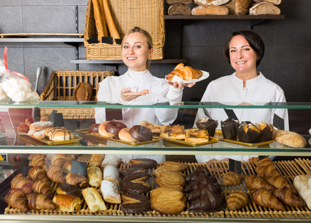 gladly: Happy woman and young girl gladly suggesting pastry in the cafeteria