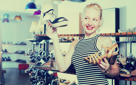 comparing: Adult woman choosing and comparing two pairs of new shoes in shop