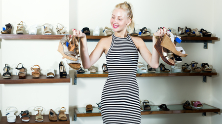 Young pretty girl shopping many shoes pairs in fashion department Stock Photo