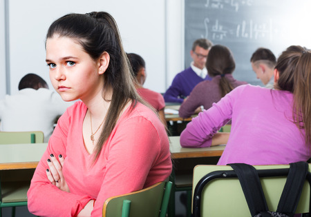 social outcast: ?lonely student sitting away from classmates and feeling depressed