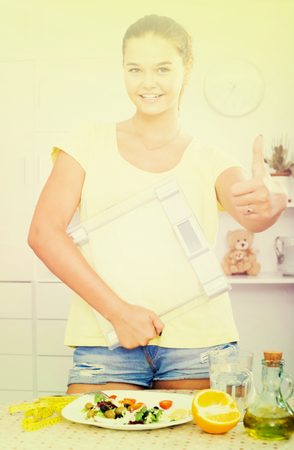 spanish looking: smiling spanish teenager girl looking satisfied and holding scale on kitchen