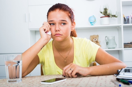sad lonely teenager girl sitting and looking at mobile phone