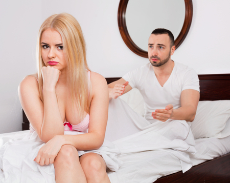 impotent: Angry beautiful young woman turned away from man complaining in bed