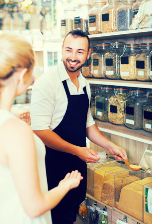 Smiling adult man seller wearing apron standing with cereals sold by weight in organic shop Stock Photo