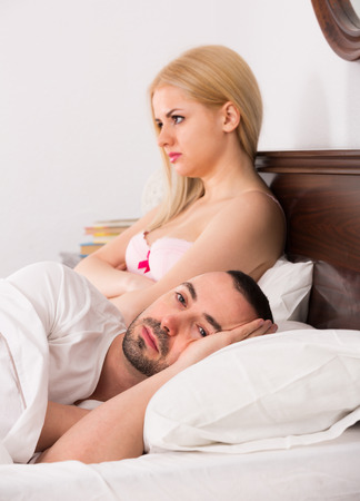 impotent: Upset young wife and  husband keeping silence in bed Stock Photo
