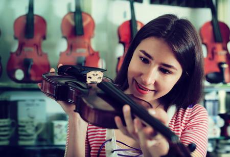 Teenage girl choosing violin in music instruments studio Stock Photo
