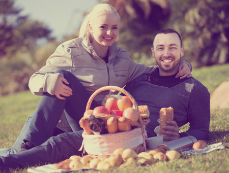 sandwitch: Smiling couple lounging in sunny spring day at picnic outdoors Stock Photo