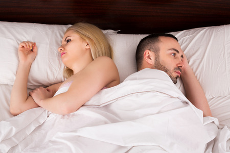 impotent: Stressed young woman and man having problems in bed Stock Photo