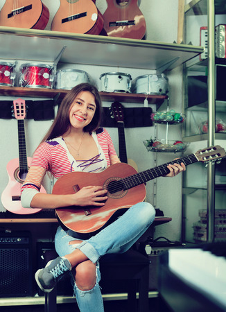 18's: Cheerful smiling teenage girl posing with classical guitar in shop Stock Photo