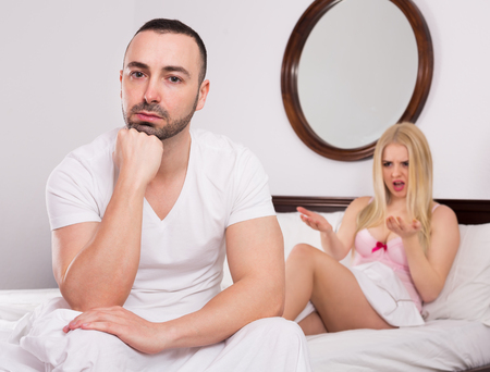 impotent: Unsatisfied wife and sad young husband having big difficulties in a bed