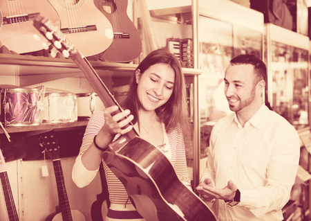 shopgirl: Friendly smiling positive shopgirl helping male client to select guitar in shop