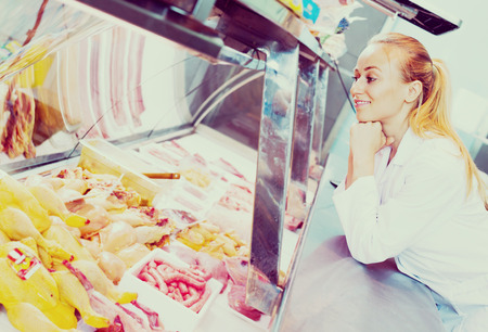 karkas: cheerful young woman wearing coat selling fresh bird carcass in delicatessen section Stockfoto