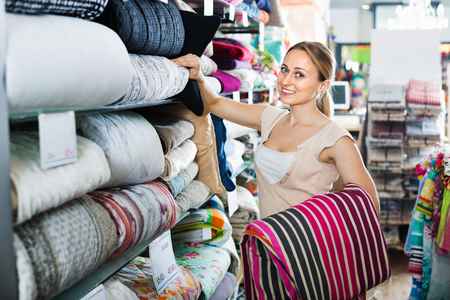 Happy smiling positive woman buying bed spread in home textile store