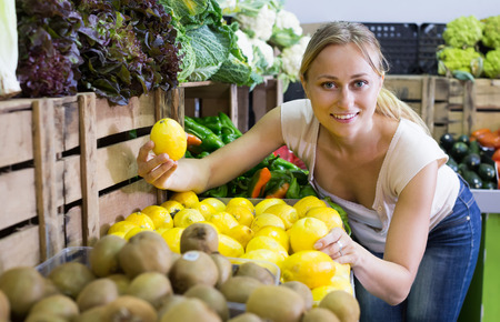 positive young woman buying fresh lemons on marketplace