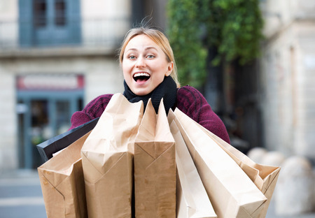 Portrait of happy  girl with many paper bags from her shopping outdoors
