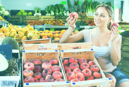Glad young charming woman customer choosing peaches on fruit market Stock Photo