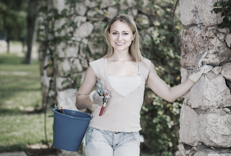 horticultural: nice young woman holding horticultural tools in garden on sunny day