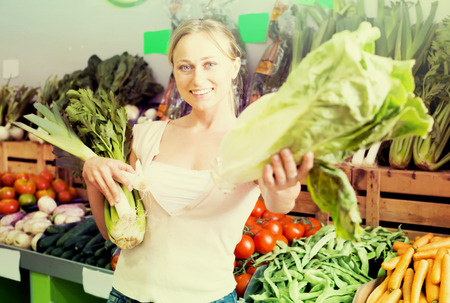 positive young female customer holding fresh celery and leek on market Stock Photo