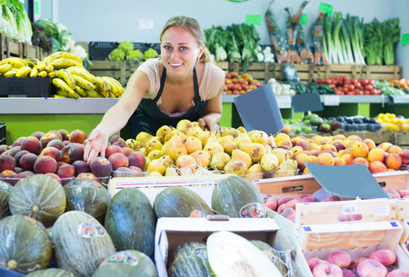 seller: cheerful young woman seller wearing apron working in fruit shop Stock Photo