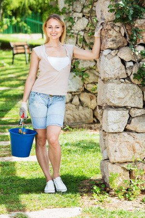 horticultural: Happy smiling young blond woman having horticultural instruments in garden on summer day Stock Photo