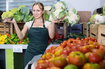 Portrait of cheerful charming  woman working in fruit shop showing fresh cabbage