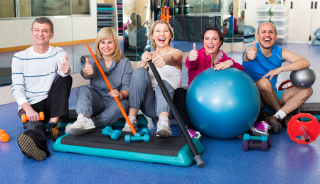 workouts: Group of  happy mature men and women after exercising in  gym with sport equipment