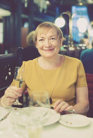 mature woman sitting: Smiling mature woman sitting in restaurant and having cold beverage