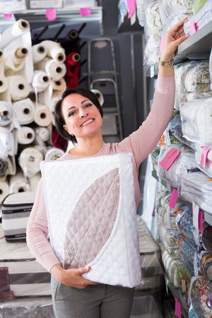 bedspread: Happy mature female customer handles bedspread near textiles shelves inside