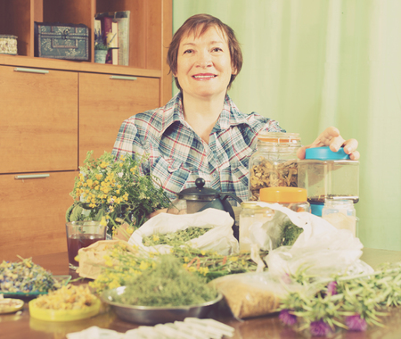 Smiling aged woman with herbs at table in home