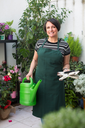 horticultural: european woman florist holding horticultural tools in gardening counter