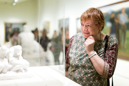 Portrait of positive mature woman attentively looking at sculptures in art museum